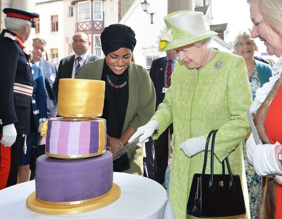 Queen Elizabeth II, right, receives a birthday cake