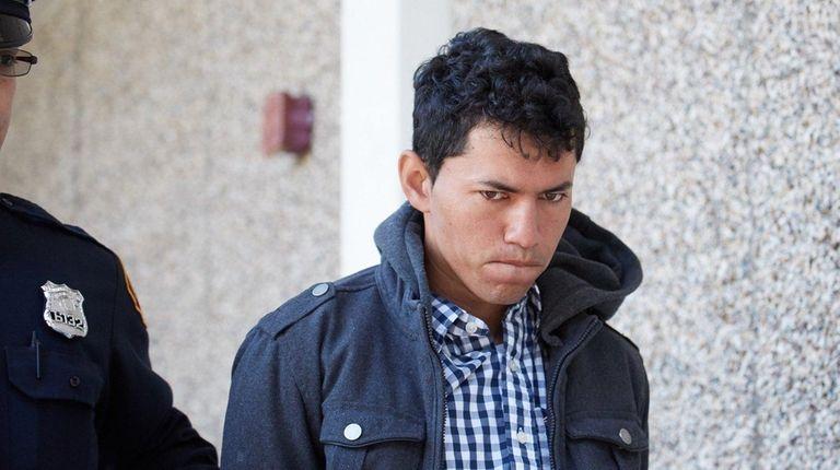 Ruddy Velasquez-Morales, 27, of Bellport, is led out