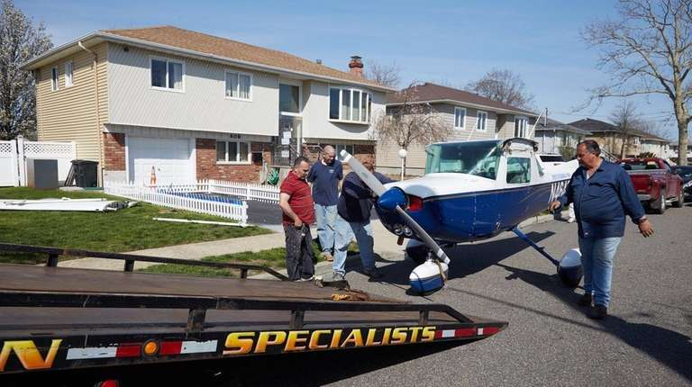 Workers remove a plane from the home of
