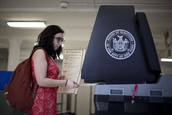 A resident casts her ballot at the P.S.