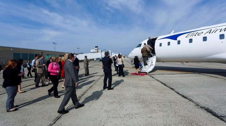 Guests board an Elite Airways plane parked for