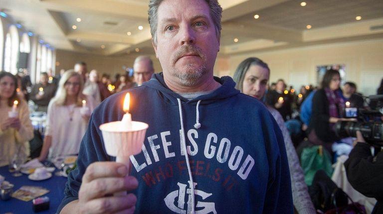 Karl Renken holds a candle at a light