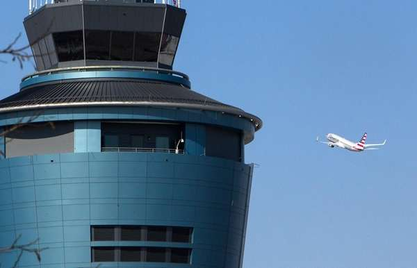 A plane passes the air traffic control tower