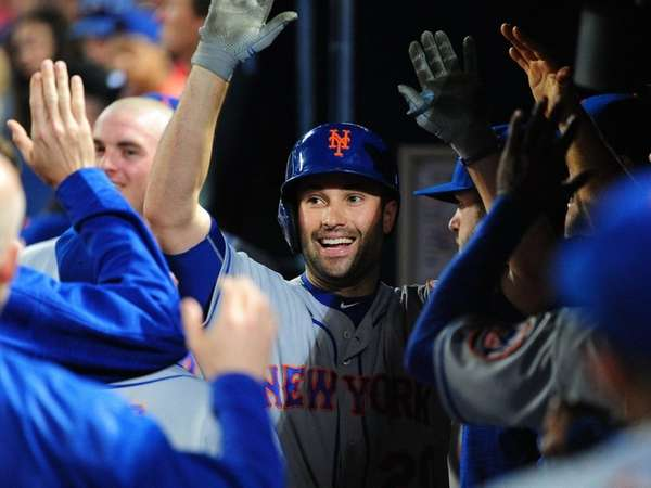Neil Walker is congratulated by Mets teammates after