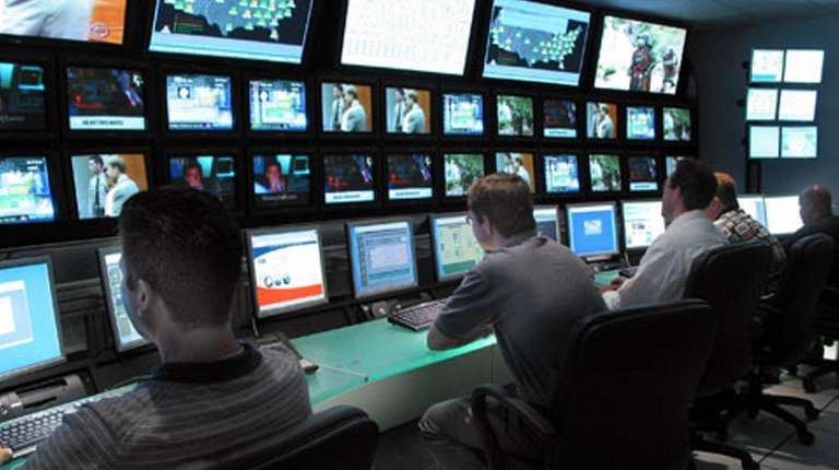 Technicians operate the console in the control room