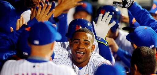 Yoenis Cespedes celebrates with teammates in dugout after