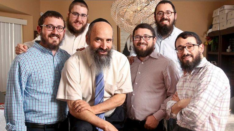 Rabbi Tuvia Teldon, 64, center, is surrounded