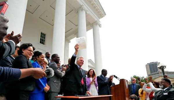 Gov. Terry McAuliffe holds up the order he