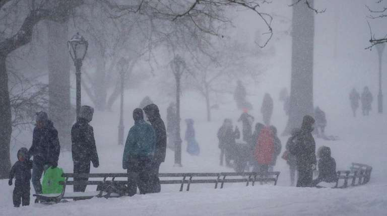 People visit Central Park as a large winter