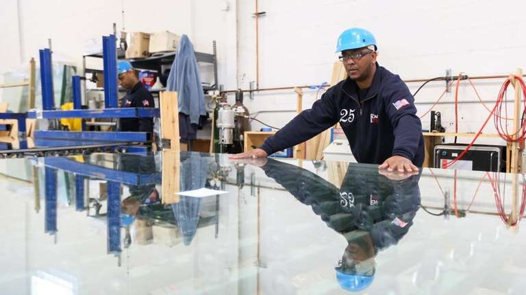 Delvis Toribio works with a panel of glass