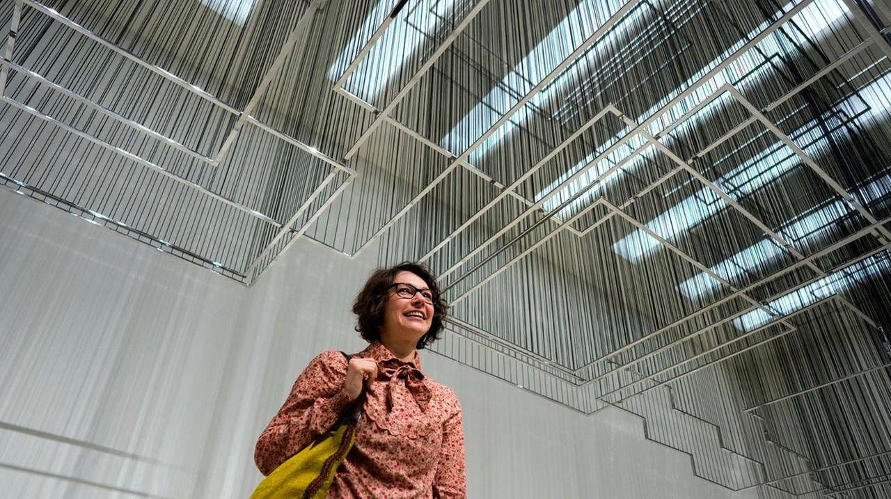 Artist Nadia Kaabi-Linke stands under her sculpture