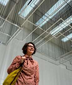 Artist Nadia Kaabi-Linke stands under her sculpture