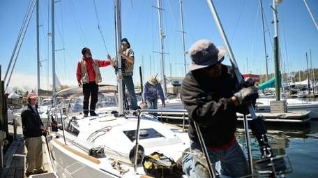 Coneys Marine employees work on a sailboat on