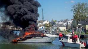 A Coast Guard boat sits near a flaming