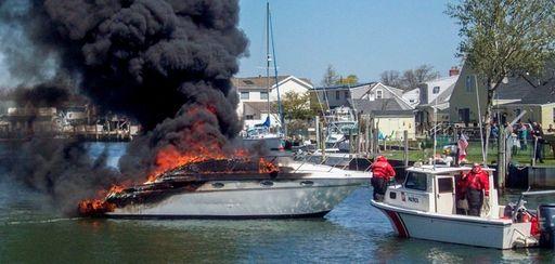 A Coast Guard boat sits near a flaming