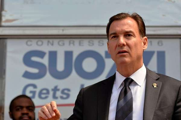 Tom Suozzi holds a news conference surrounded by