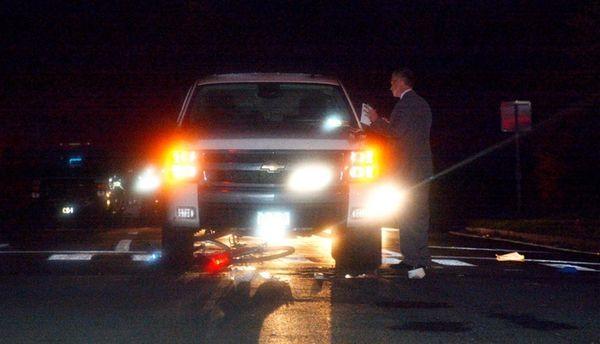 A Suffolk police investigator examines the scene where