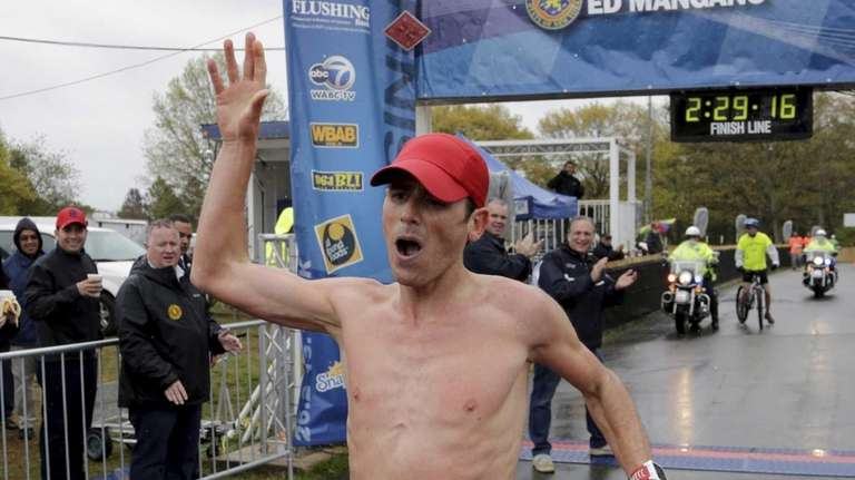 Oz Pearlman, winner of the 26.2-mile marathon, crosses