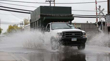 Rain-soaked pavement slows drivers on Willis Avenue in
