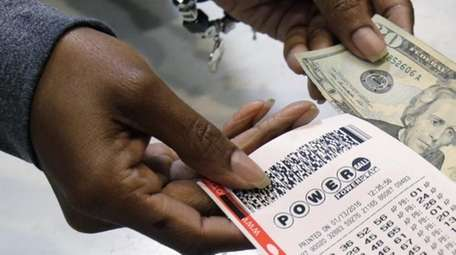 A clerk hands over a Powerball ticket for