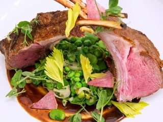 Roasted rack of lamb is served with fava