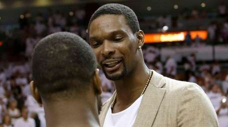 Miami Heat's Chris Bosh, right, talks to