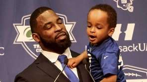 Justin Tuck holds his youngest son Jonah as