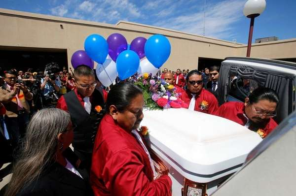 Pallbearers carry the coffin containing Ashlynne Mike on