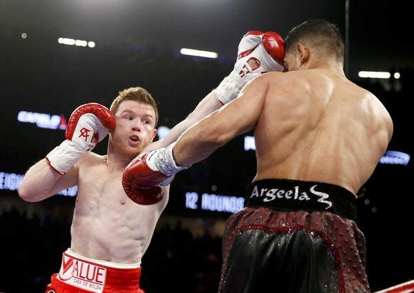 Canelo Alvarez, left, hits Amir Khan during their