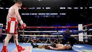 Canelo Alvarez, left, watches after knocking down Amir