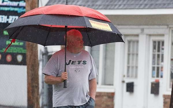 A man walks in the rain in Islip