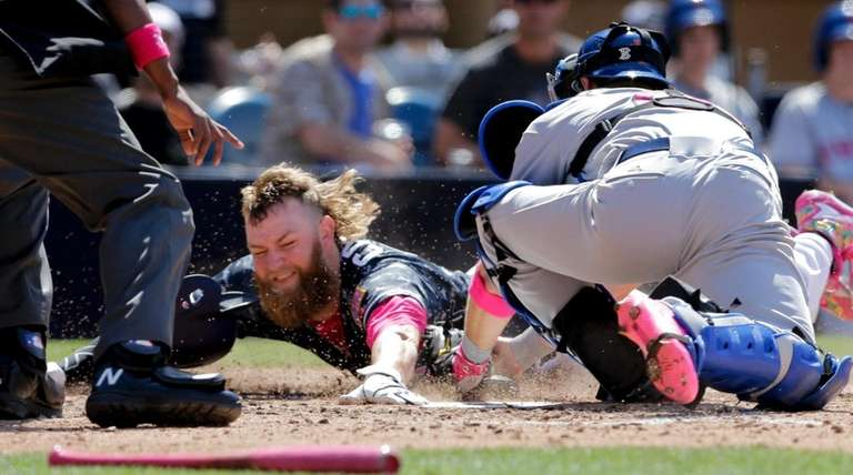 San Diego Padres' Andrew Cashner, center, is tagged
