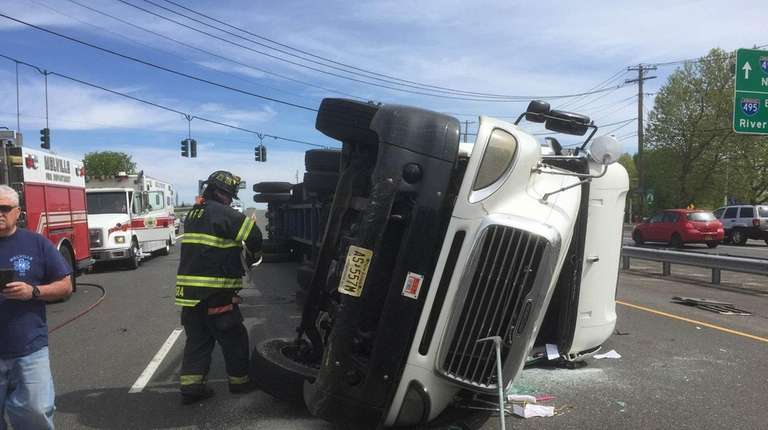 A tractor-trailer lies on its side after it