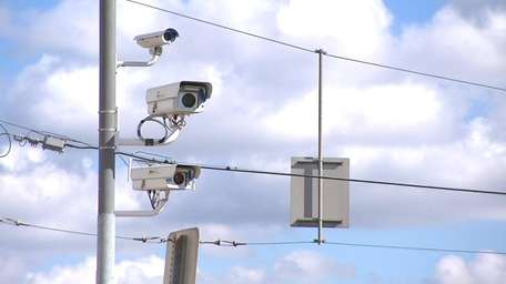 Red-light cameras hang at an intersection in this