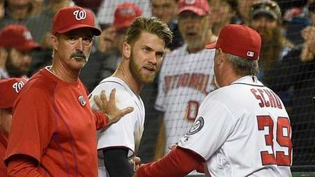 Washington Nationals' Bryce Harper, center, is restrained by