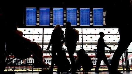 Travelers at O'Hare Airport in Chicago examine airline