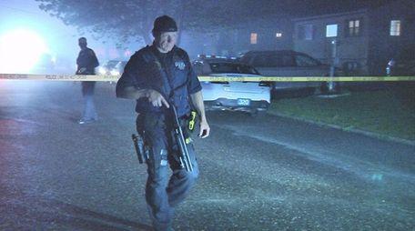 Officers walk through a Central Islip neighborhood after