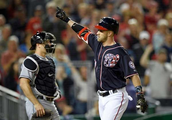 Washington's Bryce Harper crosses the plate after a