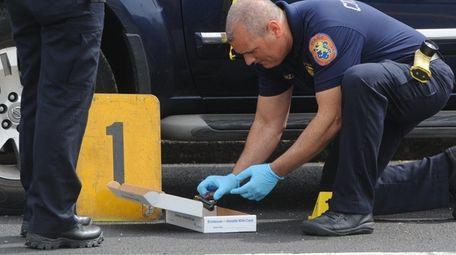 A Nassau County crime scene investigator inspects a