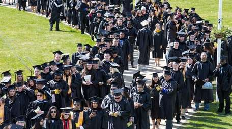 Graduates line up outside Field House of the