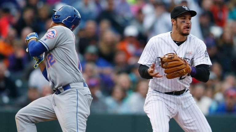 Colorado Rockies third baseman Nolan Arenado, right, looks