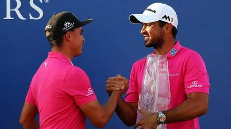 Rickie Fowler presents the trophy to Jason Day