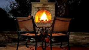 An outdoor fireplace lights up a patio and