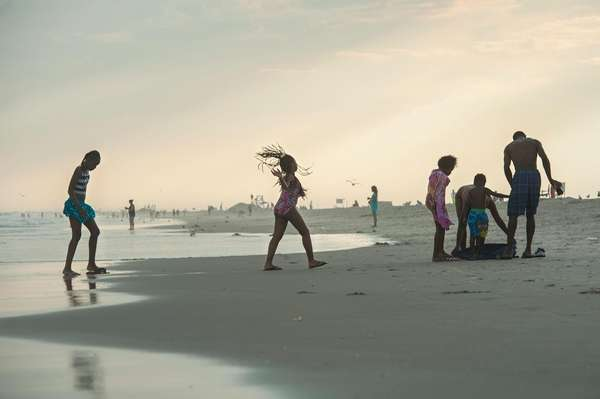 Beachgoers bask in the final moments of daylight