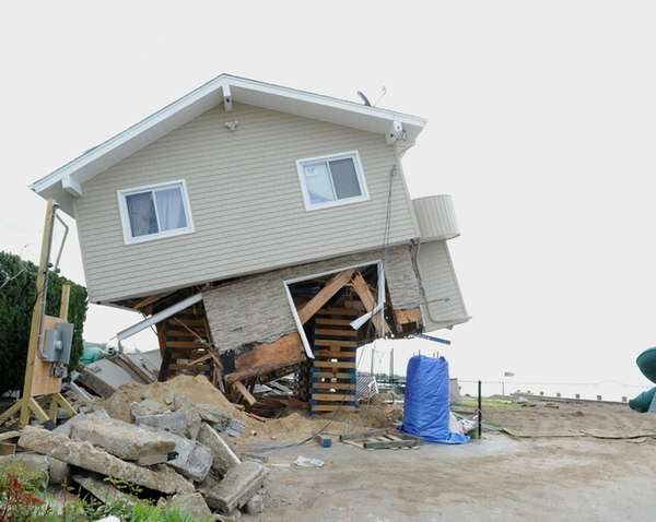 A waterfront house in Babylon hangs precariously Wednesday,