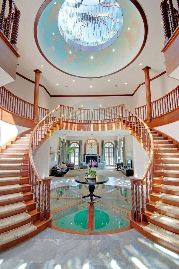 A foyer with a sweeping double staircase, a