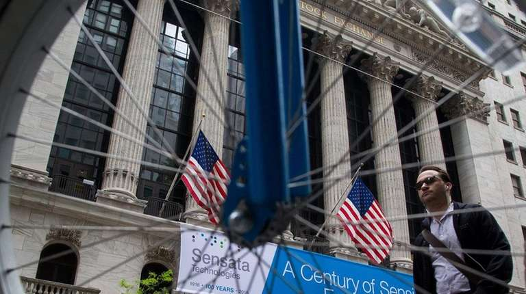 Pedestrians walk past the New York Stock Exchange