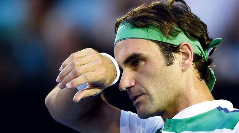 Roger Federer wipes the sweat from his face