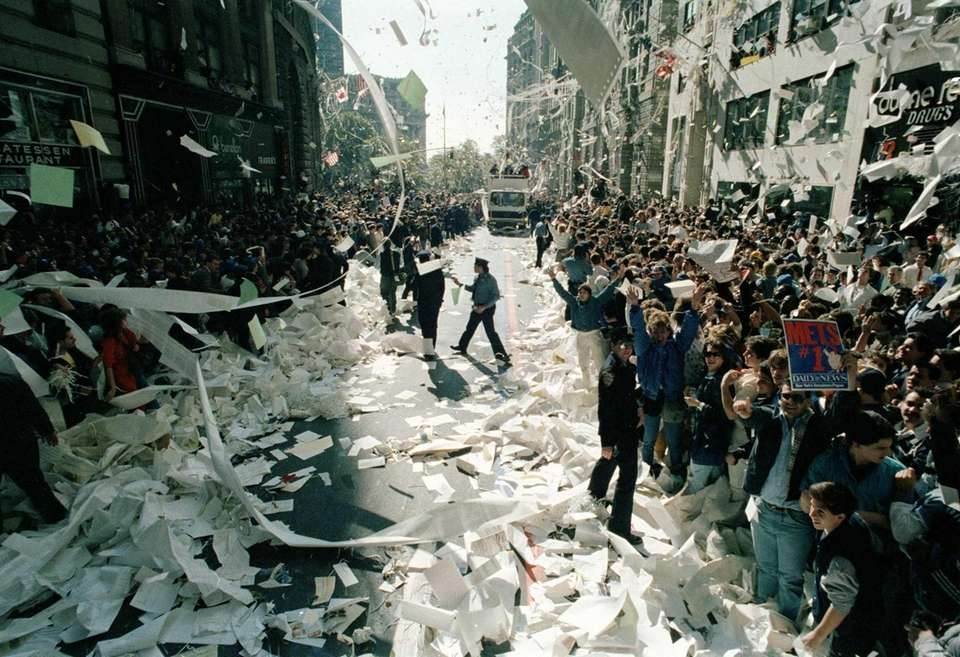 Ticker tape and paper litter a street in