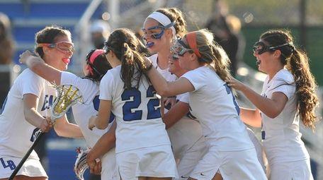 Long Beach varsity girls lacrosse teammates celebrate after